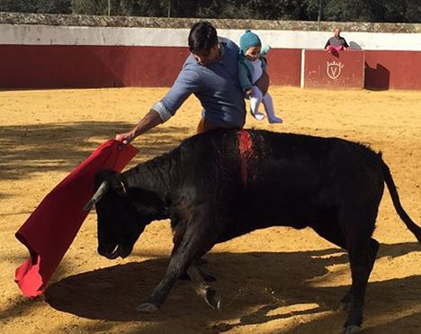 Torero mit fünf Monate alter Tochter auf dem Arm beim Stierquälen